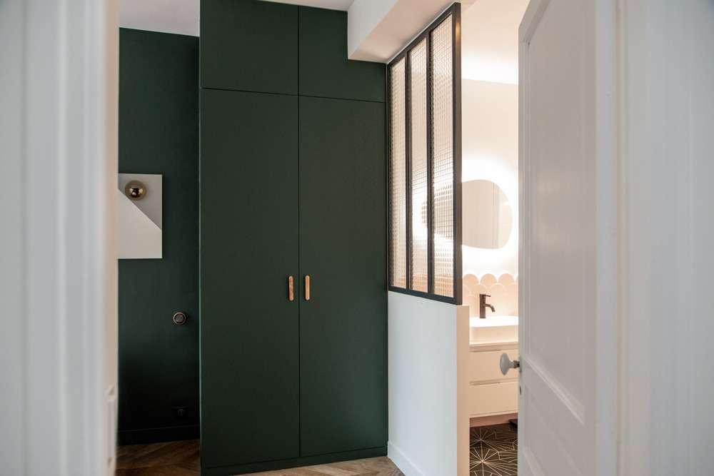 Suite parentale vert foncé ouverte sur la salle de bain par une verrière
