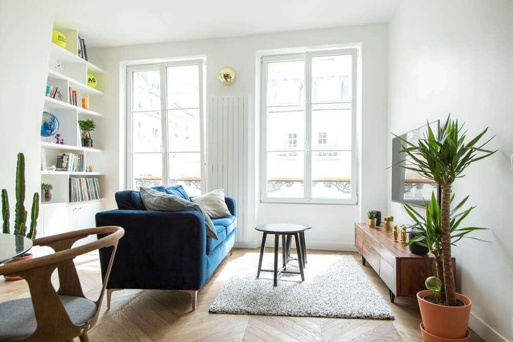 Salon contemporain avec canapé bleu en velours et parquet point de Hongrie