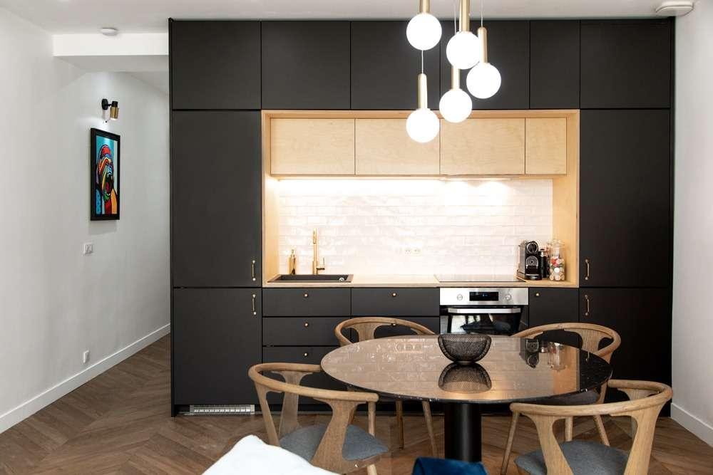 Cuisine contemporaine noir mat et bois ouverte sur la salle à manger