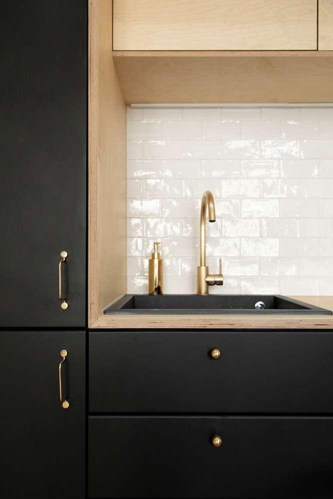 Détail de la cuisine noire mat avec robinet doré