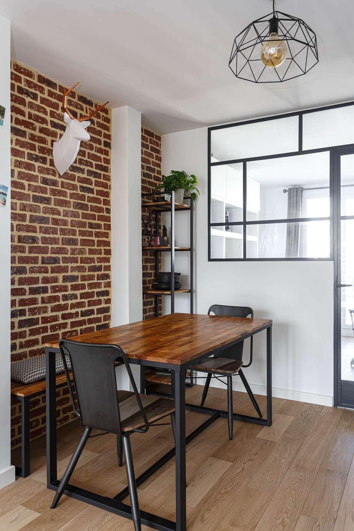 Salle à manger industrielle avec verrière et mur de briques